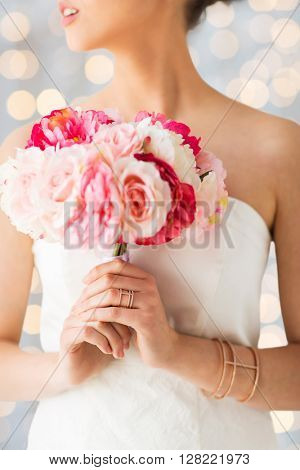 wedding, holidays, beauty, jewelry and luxury concept - close up of beautiful woman or bride with flower bouquet wearing golden ring and bracelet over holidays lights background