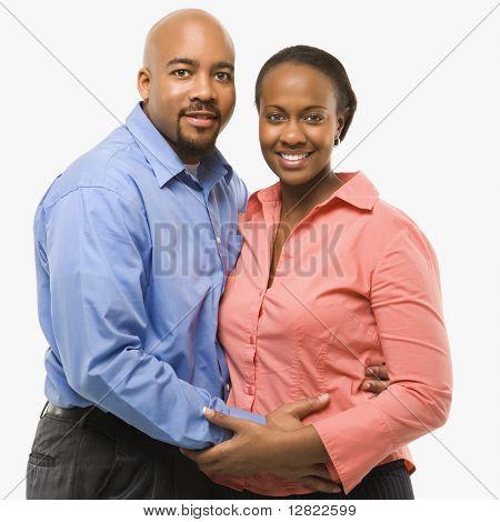 Retrato de casal de americanos africanos com os braços ao redor de um ao outro sobre fundo branco.