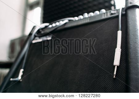 Electric guitar amplifier with silver knobs and cable closep. Selective focus technique on  professional guitar amplifier knobs