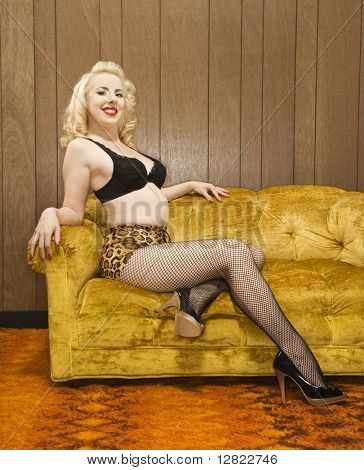 Attractive Caucasian woman in lingerie posing on retro couch.