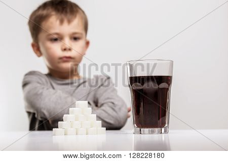 Glass full of soft drink next to it is the amount of sugar used in it