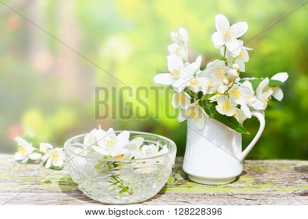 Gentle jasmine in small porcelain jug and glass bowl