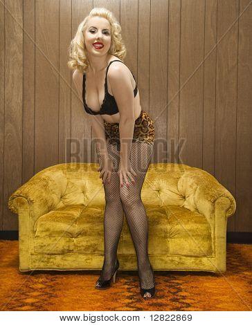 Attractive Caucasian woman in lingerie posing in retro room.