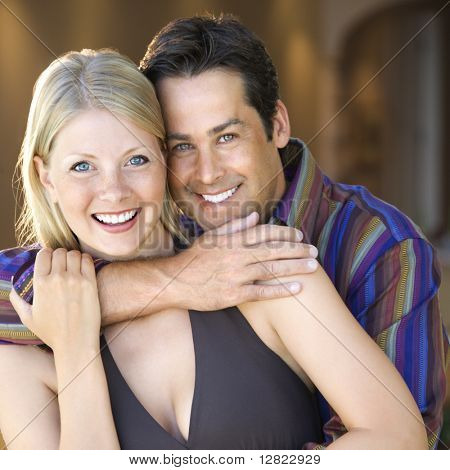 Caucasian mid adult couple embracing and smiling at viewer.