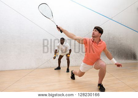 Students playing squash on court. Handsome men in sports wearing holding rackets while entertaining themselves.