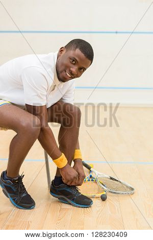 Happy squash player man looking at camera and smiling while preparing for squash game on court. Black man and squash.