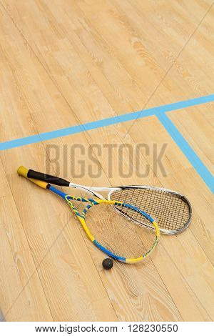 Closeup of squash rackets and one ball on wooden background. Top view of special equipment for squash game.