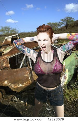 Sexy tattooed Caucasian woman yelling and holding her hands over her ears in junkyard.