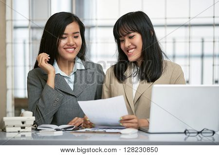 close up image of two businesswomen working and discussing in office