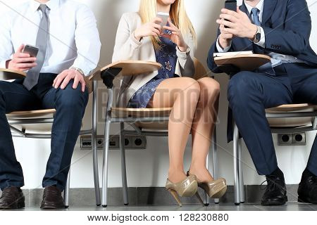 Business colleague sitting on chairs and using mobile phone.