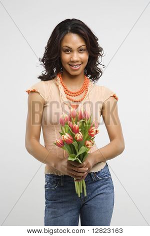 Studio shot of multiethnic mid-adult stylish woman holding bouquet of tulips smiling and looking at viewer.