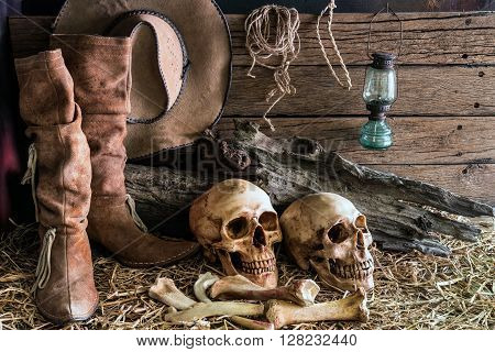 still life two human skull on hay with traditional leather boots and american west rodeo brown felt cowboy hat background vintage and dark tone for horror halloween