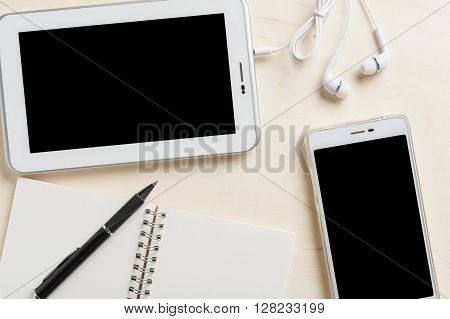 Small tablet pc with blank area on touchscreen smart phone in ear headset notebook and pen on wood table