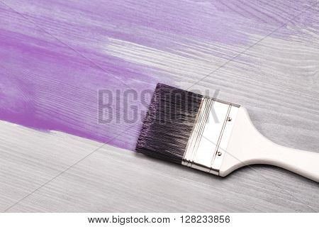Painting white wooden surface with white paintbrush and violette of lavender color.