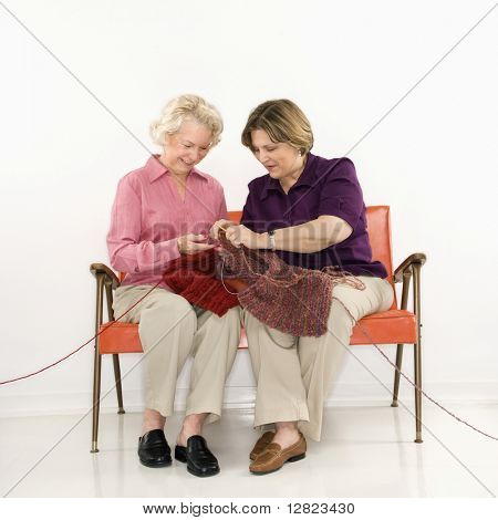 Caucasian middle aged woman and senior woman sitting and knitting.