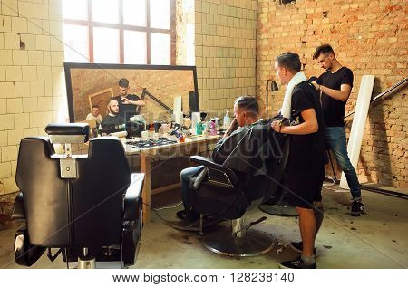 KYIV, UKRAINE - OCT 5, 2015: Young guys making haircuts in the hipster style barber shop with grunge walls on October 5, 2015. Kiev is the 8th most populous city in Europe.