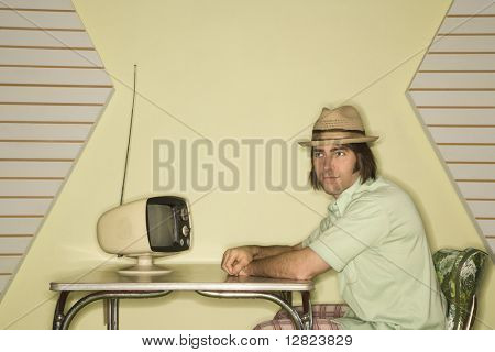 Caucasian mid-adult man wearing hat sitting at 50's retro dinette set in front of old television.