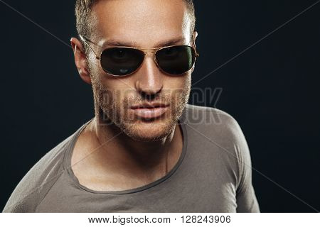 Handsome man wearing sunglasses in the studio on a dark background