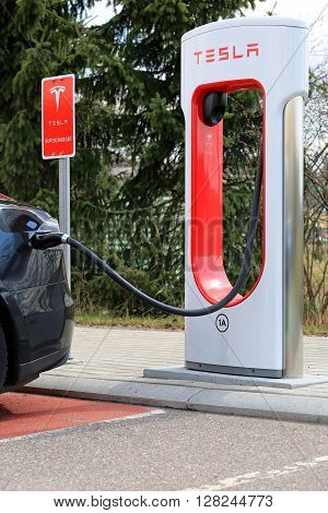 PAIMIO, FINLAND - APRIL 29, 2016: Tesla Supercharger Station with black Tesla Model S electric vehicle being charged. Charging the battery from 10 to 80 percent takes about 40 minutes.
