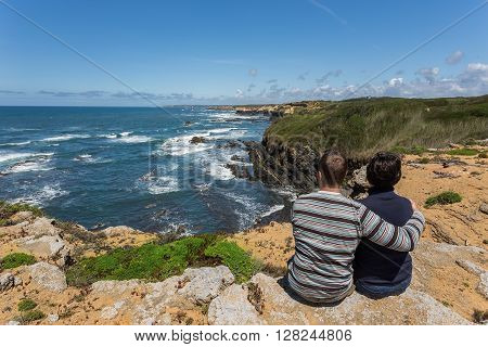 Couple resting on a rocky shore. View of the Atlantic sea