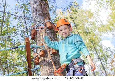 happy boy overcoming fear of heights. smiling child engaged climbing high wire park