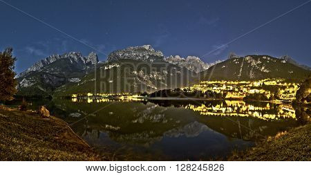 Night landscape of Molveno lake and Dolomiti di Brenta Group in a quiet summer evening with starry sky in the background Trentino - Italy