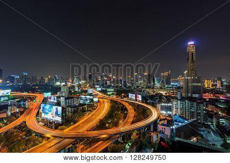 BANGKOK THAILAND - 16 APRIL 2016 - Scene of Bangkok high-rise buildings and traffic light trails on expressway at dusk.
