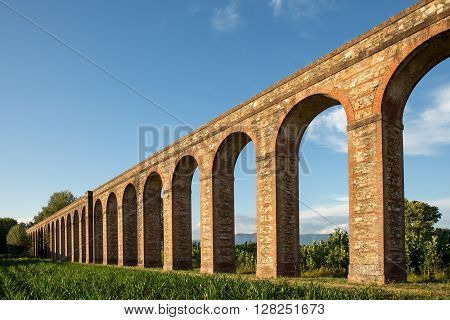 Ancient Aqueduct - Section of the Nottolini Aqueduct in Tuscany near Lucca Italy. Warm evening light with classic Tuscan textures and tones. Concepts could include Travel Architecture Europe others.