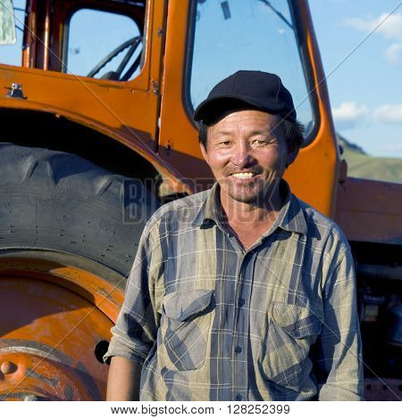 Smiling Mongolian Farmer Standing Tractor Concept