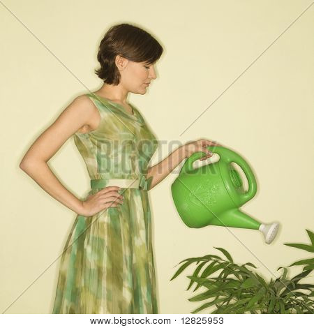 Pretty Caucasian mid-adult woman wearing vintage dress watering houseplant with green watering can.