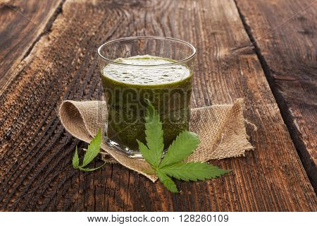 Healthy cannabis smoothie on wooden background. Natural supplement detox and healthy living.