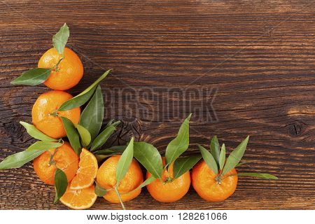 Fresh ripe mandarines with green leaves and copy space on wooden background. Organic fresh mandarines healthy fruit eating.