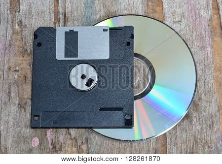 floppy disk and compact disc on wood board