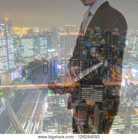 Double exposure of Business man with laptop and cityscape