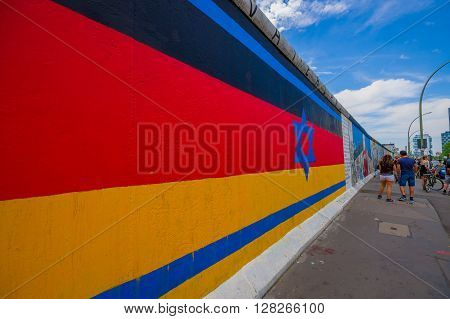 BERLIN, GERMANY - JUNE 06, 2015: Berlin wall actually is a white paper for people to express theirselves, on the wall germany colors flag with Davids star in the middle on blue