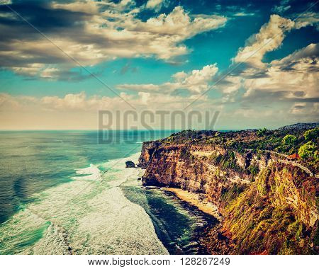 Vintage retro effect filtered hipster style image of Uluwatu cliff in ocean on sunset. Bali, Indonesia