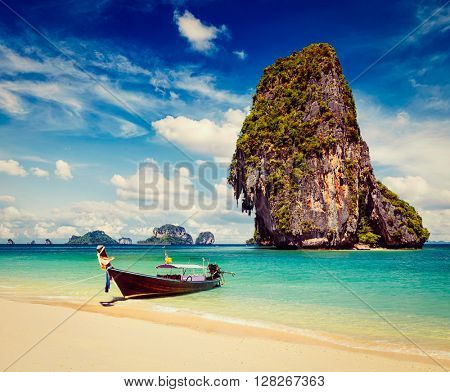 Thailand tropical vacation concept background - Vintage retro effect filtered hipster style image of long tail boat on tropical beach with limestone rock, Krabi, Thailand