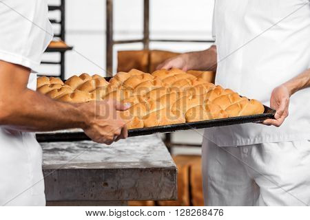 Midsection Of Baker's Carrying Breads In Tray