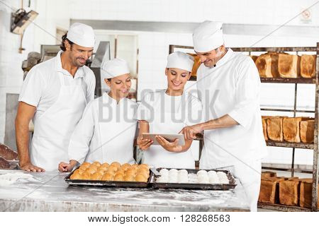 Male And Female Baker's Using Digital Tablet In Bakery