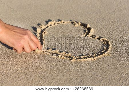 Female Hand Drawing Shape Of Heart On Sand