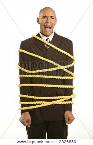 African American businessman screaming wrapped in yellow rope.