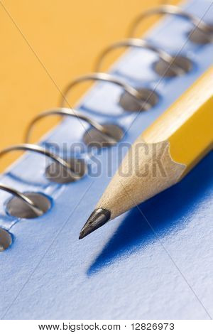Close up of sharp pencil placed on blue spiral bound notebook.