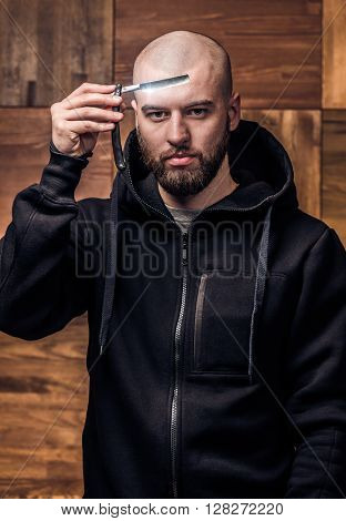 Portrait of brutal bald man with vintage straight razor on a wooden texture in barbershop. Portrait of hipster holding straight edge razor against wooden wall. poster