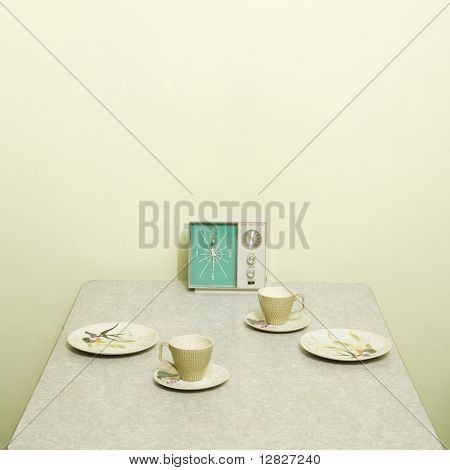 Retro 50's table setting with dishes coffee cups and vintage clock radio.
