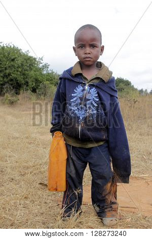 January 20 2016 Village Pomerini in Tanzania-Africa-An unidentified African child goes to fill her tank of drinking water. Many times this requires hours of walking.