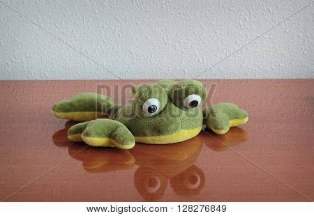 Plush toy frog lying at the table. Shallow depth of field.
