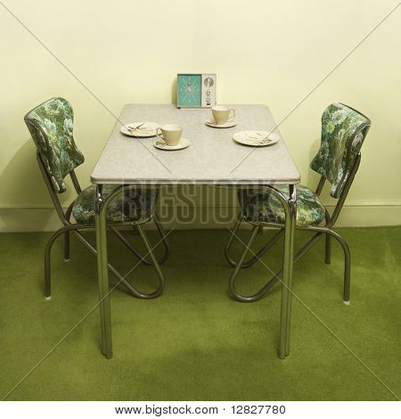 Retro 50's formica and chrome dinette set with green vinyl chairs.