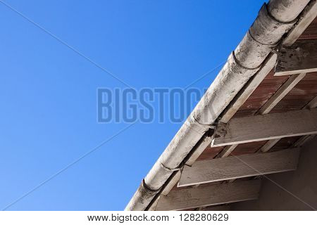Dirty old peeling gutters and roof trusses