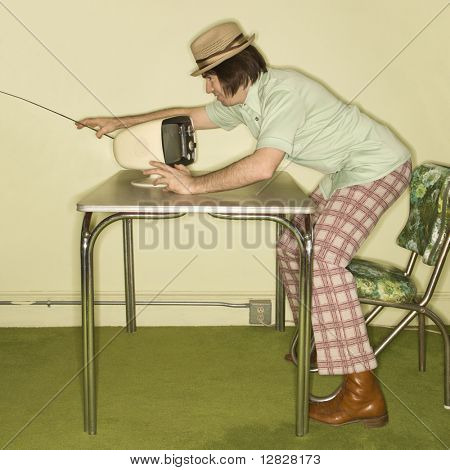Side view of Caucasian mid-adult man wearing hat and plaid pants leaning over 50's retro dinette set adjusting old television set.