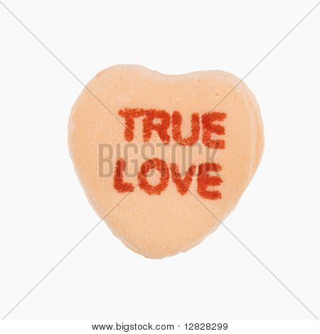 Orange candy heart that reads true love against white background.